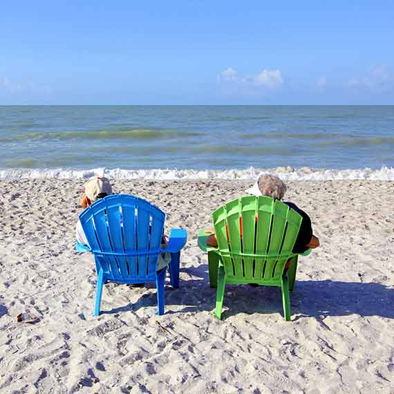 man and woman sitting on beach enjoying view of Gulf of Mexico
